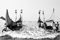 A group of Rohingya men push their fishing boats out to sea.  Most Rohingya men in the Shamlapur area of Bangladesh work as bonded laborers and are trapped into debt to local Bangladeshi boat owners. (2008)