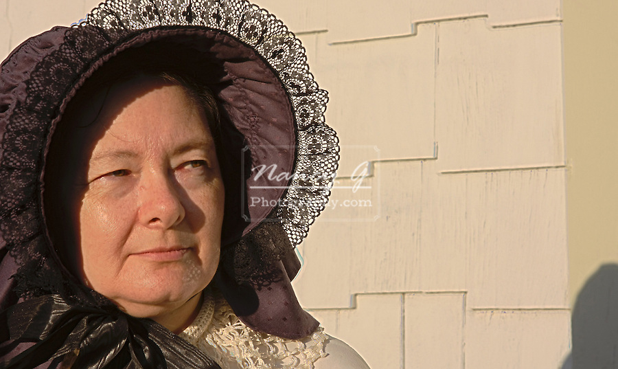 A lady wearing a bonnet dressed in 1800s time period on a house porch