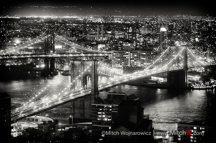 Brooklyn Bridge at night in New York City between Mahnattan at left and Brooklyn across river at right.  Manhattan bridge in background.©Mitch Wojnarowicz Photographer..Not a royalty free image. COPYRIGHT PROTECTED.www.mitchw.com.518 843 0414_Mitchw@nycap.rr.com.20090321