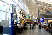 Shiny new Hong Kong airport with stores and high tech items as travelers come and go in clean shiny environment termina
