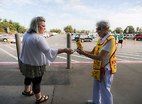 NWA Democrat-Gazette/CHARLIE KAIJO Tanya Lucas of Rogers (from left) makes a donation to Jean Schmitz of Bella Vista during a Tootsie Roll drive, Friday, October 5, 2018 at Walmart in Rogers.<br /><br />The Knights of Columbus is kicking off their annual tootsie rool drive Friday. The fundraiser runs through Oct. 13. They hand out Tootsie Rolls and accept donations, similar to the VFW poppy campaign.