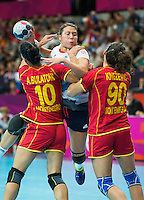 28 JUL 2012 - LONDON, GBR - Ewa Palies (GBR) of Great Britain (centre, in white, blue and red) finds her path to goal blocked by Andjela Bulatovic (MNE) (left) and Milena Knezevic (MNE) (right) both of Montenegro during the women's London 2012 Olympic Games Preliminary round handball match at The Copper Box in the Olympic Park, in Stratford, London, Great Britain .(PHOTO (C) 2012 NIGEL FARROW)
