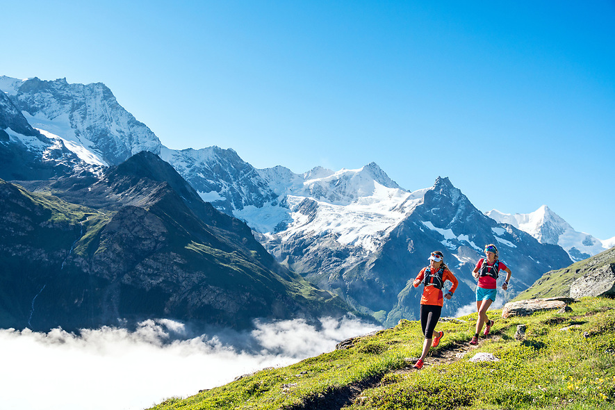 Trail running above Zinal, Switzerland on a sunny summer morning with snow covered mountains in the background.