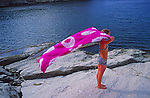 Model Released young girl holding purple tie dye cloth in the wind by the sea Sicily, Italy