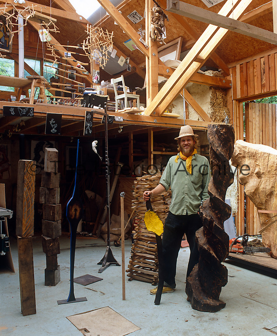Portrait of sculptor Henry Brudenell-Bruce standing amongst his sculptures in his studio