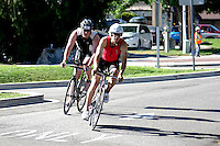 These two triathletes are approaching the finishline of the biking portion of a Chelanman Triathlon.