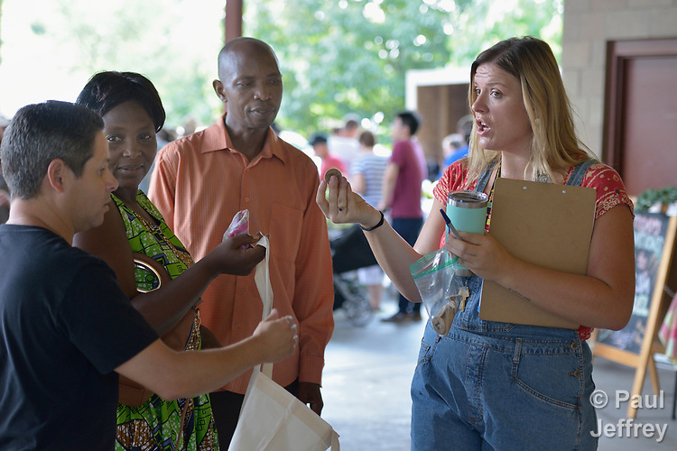 Monique Lohmeyer (right), a case manager for Church World Service, explains the use of tokens to refugees from Rwanda and Cuba in the Durham Farmers' Market in Durham, North Carolina. The Double Bucks program allows consumers with EBT cards to double their purchasing power.<br /> <br /> Church World Service resettles refugees in North Carolina and throughout the United States.<br /> <br /> Photo by Paul Jeffrey for Church World Service.