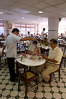 Waiter pouring hot milk from a kettle into a customer's cafe con leche at the Gran Cafe de la Parroquia, Veracruz city, Mexico