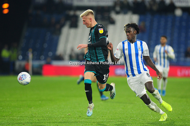 Sam Surridge of Swansea City battles with Trevoh Chalobah of Huddersfield Town during the Sky Bet Championship match between Huddersfield Town and Swansea City at The John Smith's Stadium in Huddersfield, England, UK. Tuesday 26 November 2019
