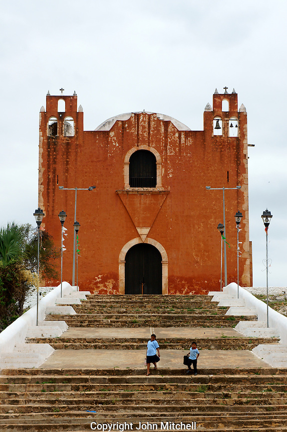 Two Mexican school children in front of the Spanish colonial church in Santa Elena, Yucatan, Mexico