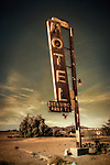 Desert location with rusty old motel sign on roadside