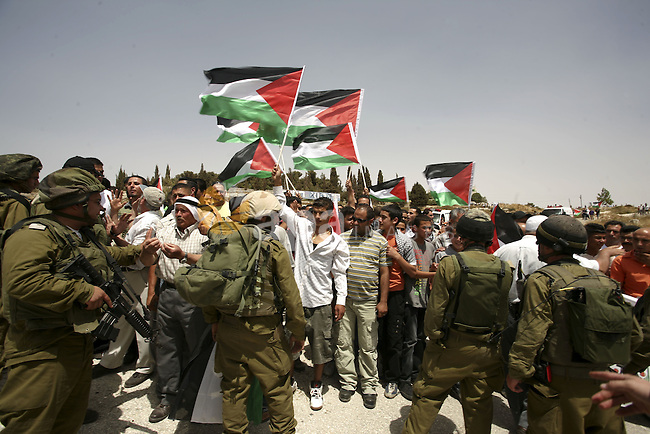 Israeli soldiers surround Palestinians from the village of Bet In, north of Ramallah, as they hold up their national flag during protest against Israeli occupation on June 11, 2010 near the Jewish settlement of Beit El. Photo by Eyad Jadallah