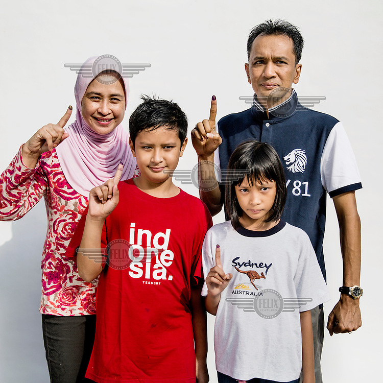 A family flashes a single finger sign, symbolising Indonesian presidential candidate Prabowo Subianto's candidacy number after the husband and wife cast their votes at a polling station in Jakarta.