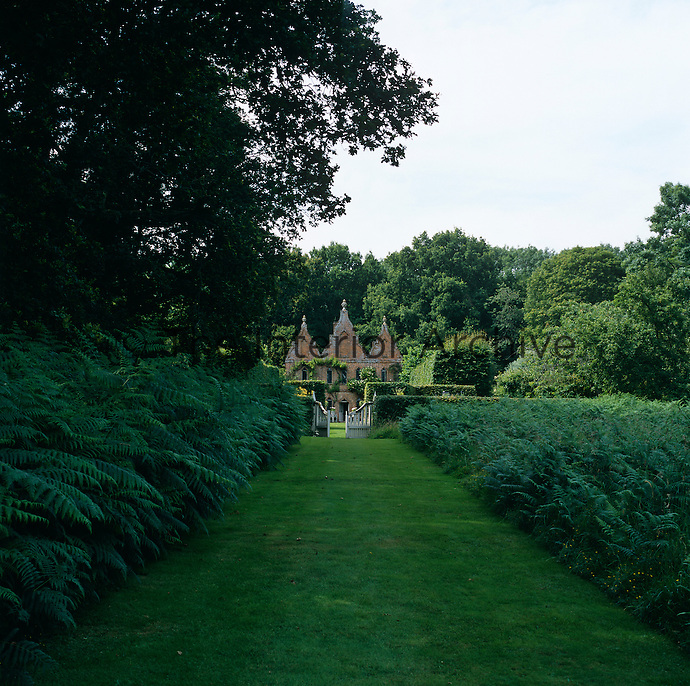View up the manicured grass path between banks of fern to the Jacobean-Revival red brick facade which was added to the hunting lodge in 1720