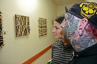 Ronnie Shaw of Apogee  Piercing in Ocean Beach and friend Mary look at the artwork of Patrick Kennedy on display in Craves Cafe as part of the Newport Nights Art Happening in Ocean Beach, Saturday January 26, 2008