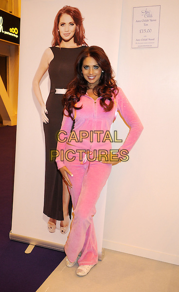 Amy Childs .Poses at her stand at the Vitality Show, Earls Court, London, UK, .March 21st 2013..full length pink velour tracksuit trackie casual sportswear hoodie bottoms  hand on hip poster advertising her spray tan .CAP/PPBK.©Bob Kent/PP/Capital Pictures