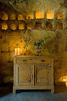 An old stripped and scrubbed pine cupboard stands beneath two rows of square niches filled with tealights