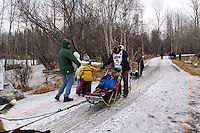 Trent Herbstand team run past spectators on the bike/ski trail with an Iditarider in the basket during the Anchorage, Alaska ceremonial start of the 2015 Iditarod race. Photo by Ed Bennett/IditarodPhotos.com