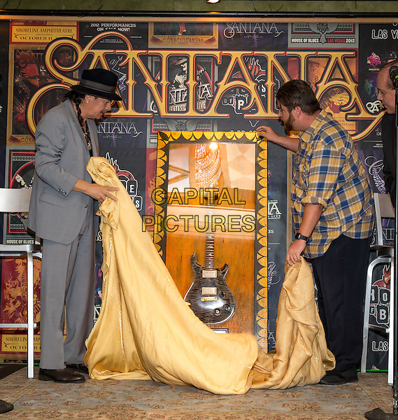 LAS VEGAS, NV - November 3: ***HOUSE COVERAGE*** <br /> Carlos Santana pictured as House of Blues executives honor Santana with the a commemorative display marking the sale of his 100,000th ticket to An Intimate Evening with Santana: Greatest Hits Live at House of Blues Las Vegas at Mandalay Bay Resort in Las Vegas, NV on November 3, 2015. <br /> CAP/MPI/EKP<br /> &copy;EKP/MPI/Capital Pictures