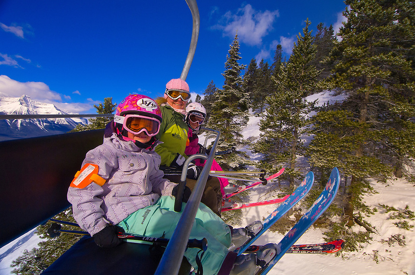 Children and their mother ride the chairlift at Lake Louise Mountain Resort, Lake Louise, Banff National Park, Alberta, Canada