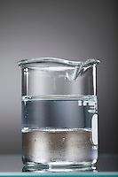 DENSITY OF MERCURY AND WATER COMPARED<br /> Demonstration of Immiscibility.<br /> Mercury is poured from graduated cylinder into flask. When water is poured after mercury, the density of mercury prevents the water from permeating to form solution. This experiment demonstrates immiscibility and phase differences in these two liquids.