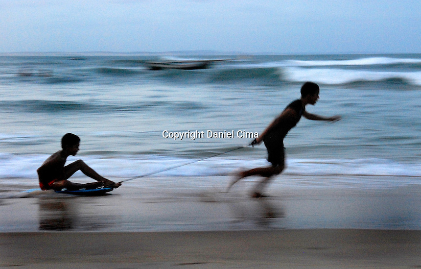 Teenagers playing at the beach in Pipa, Brazil