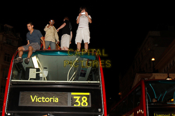 FANS.Spanish Football fans celebrate as Spain win the World Cup for the first time in history, Piccadilly Circus, London, England, UK, July 11th 2010..full half length fan atmosphere climbing on roof top of double decker bus 38 standing.CAP/MAR.© Martin Harris/Capital Pictures.