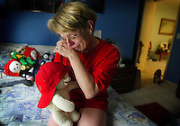 As she sits in her son's empty room, Cheryl Downs clutches a bear which has the hat her son, 17 year-old Ryan Martin, was wearing when he was killed in a car accident December 23, 2001. Downs, speaking from her Ormond Beach home Tuesday morning, June 4, 2002, stresses the importance of safety belts to teenage drivers so other parents may not experience the trauma of losing their children in auto accidents.(kelly Jordan)..**FOR AUTUMN STORY**