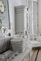 Detail of a white-painted picnic basket on a console table in the bedroom with a large wardrobe in the background