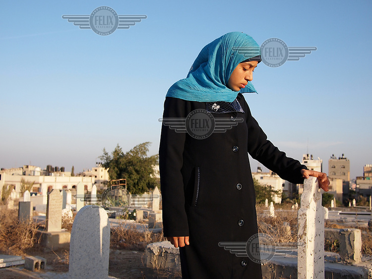 """Amira Al-Qerem (16) visits the grave of her father, sister and brother in Gaza City on October 26 2010. Amira was missing and presumed dead after she was injured by one of the same explosions that killed her father, brother and sister during the last days of the Israeli invasion of Gaza in 2009. She was found three days later, after her family thought they had buried her remains with those of the other three. She is one of the main subjects of the controversial documentary film """"Tears of Gaza"""" by director Vibeke Løkkeberg."""