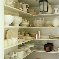 A walk-in cupboard is filled with a variety of porcelain, silverware and glass