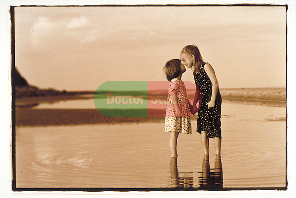 smiling young girls embrace at beach