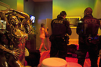 "Switzerland. Geneva. Two police officers check at night the identity of a customer in the Paquis neighborhood, known for its nightlife and Red-light district. Street prostitution. Most of the prostitutes work in the streets. Others wait inside seated on sofas and look through the windows for customers. Prostitution is often referred to as ""the world's oldest profession"". Both policemen are wearing a ballistic vest, bulletproof vest or bullet-resistant vest which is an item of personal armor that helps absorb the impact from knives, firearm-fired projectiles and shrapnel from explosions, and is worn on the torso. Soft vests are made from many layers of woven or laminated fibers and can be capable of protecting the wearer from small-caliber handgun and shotgun projectiles. 19.03.12 © 2012 Didier Ruef"