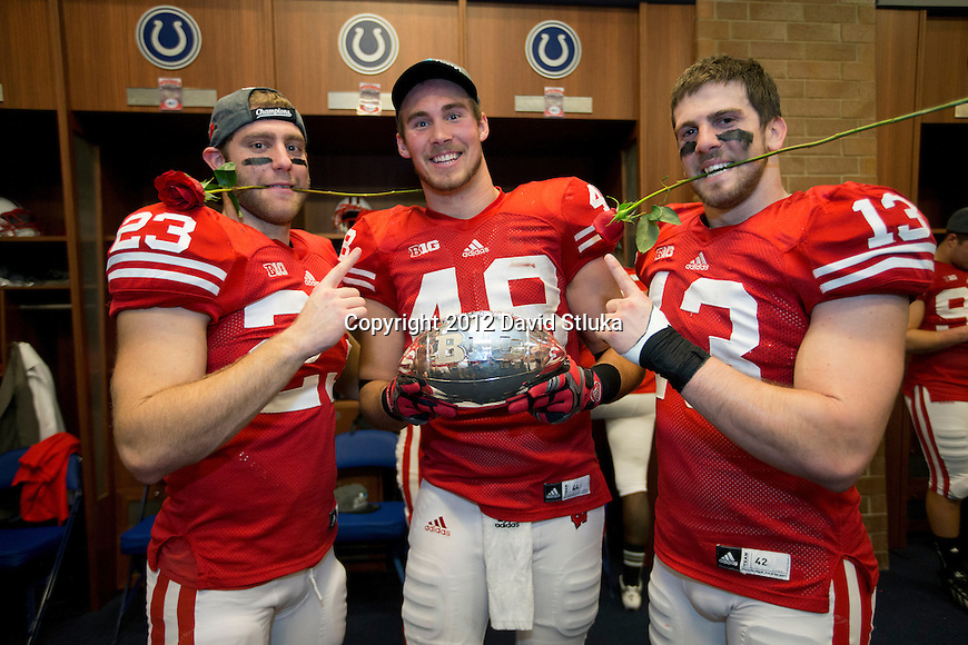 Wisconsin Badgers teammates Jerry Ponio (23), Jacob Pedersen (48) and Conor O'Neill (13) pose with the Big Ten Championship Trophy after the Big Ten Football Championship NCAA football game against the Nebraska Cornhuskers Saturday, December 1, in Indianapolis. The Badgers won 70-31. (Photo by David Stluka)