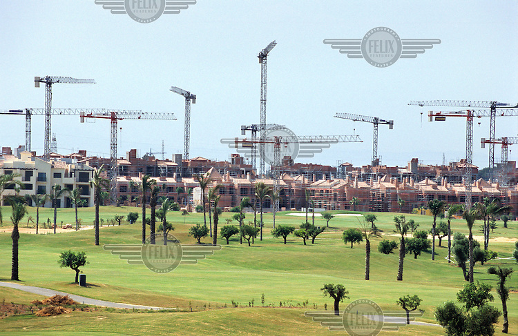 Construction cranes loom above the golf course of a new apartment complex in Los Alcazares. In recent years there has been an explosion of controversial tourist-focused developments in Spain's arid southeastern region causing environmental degradation and placing enormous pressure on the limited water supplies in the area.