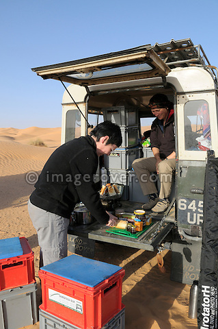 Africa, Tunisia, nr. Ksar Rhilane. Desert tourists Kerstin and Doris preparing breakfast on the rear tailboard of their historic 1962 Land Rover 88. --- No releases available, but releases may not be needed for certain uses. Automotive trademarks are the property of the trademark holder, authorization may be needed for some uses.  --- Info: Image belongs to a series of photographs taken on a journey to southern Tunisia in North Africa in October 2010. The trip was undertaken by 10 people driving 5 historic Series Land Rover vehicles from the 1960's and 1970's. Most of the journey's time was spent in the Sahara desert, especially in the area around Douz, Tembaine, Ksar Ghilane on the eastern edge of the Grand Erg Oriental.