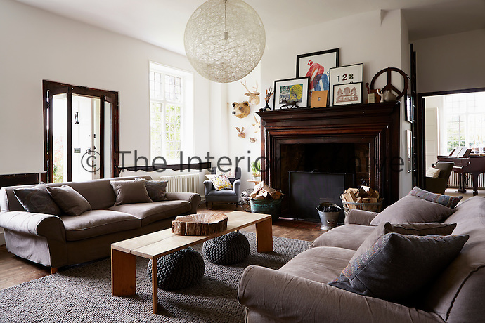 A living room with two large facing sofas, laden with matching pillows. A bench by Mark Tuckey sits in between.