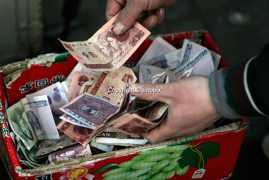 A vendor counts Chinese RMB spare changes in a Beijing street, China..