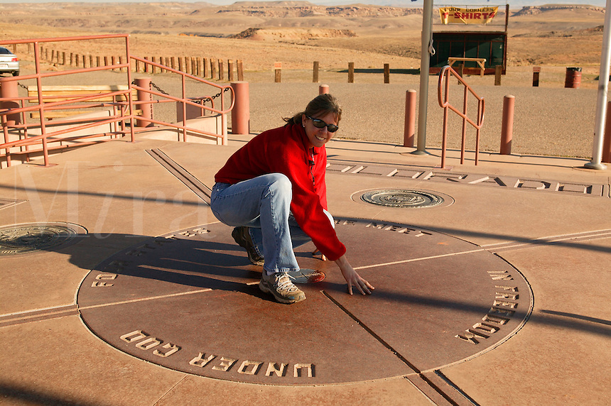 A visitor in four states at once at Four Corners, the point where Colorado, Arizona, New Mexico and Utah state lines all meet.  (model released