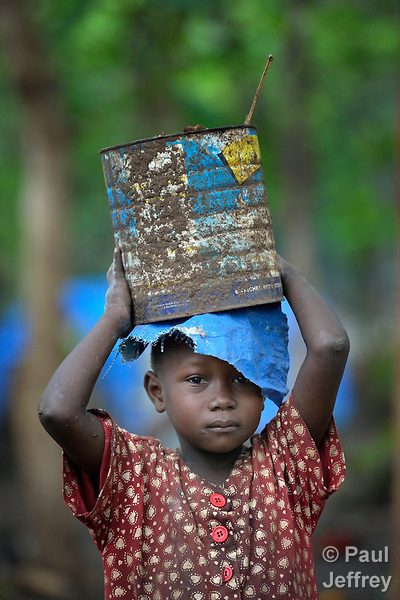A girl carries a can on her head in a camp for more than 5,000 displaced people in Riimenze, in South Sudan's Gbudwe State, what was formerly Western Equatoria. Families here were displaced at the beginning of 2017, as fighting between government soldiers and rebels escalated.<br />