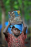 A girl carries a can on her head in a camp for more than 5,000 displaced people in Riimenze, in South Sudan's Gbudwe State, what was formerly Western Equatoria. Families here were displaced at the beginning of 2017, as fighting between government soldiers and rebels escalated.<br /> <br /> Two Catholic groups, Caritas Austria and Solidarity with South Sudan, have played key roles in assuring that the displaced families here have food, shelter and water.