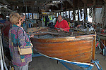 Man working and talking to visitors at Everson´s traditional boatyard, Woodbridge, Suffolk, England