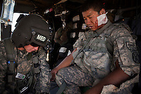 A US Army medic from Charlie Company, Sixth Battalion, 101st Aviation Regiment treats a US Soldier SPC Santisouk Champada, Charley Troop, 1-71 Cav, 1st Brigade Combat Team, 10th Mountain Division who was injured in an IED (improvised explosive device) blast, on a medevac helicopter rescue mission near Kandahar.