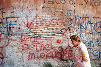 Italy. Province of Lazio. Rome. Santa Maria della Pieta is an asylum for mentally handicapped people. A woman rests against a colorful wall covered by graffitis. Mental hospital. Lunatic asylum. Psychiatric hospitals, also known as mental hospitals, are hospitals specializing in the treatment of serious mental disorders. Santa Maria della Pieta is specialised in the temporary or permanent care of residents who, as a result of a psychological disorder, require routine assistance, treatment, or a specialised and controlled environment. Patients are often admitted on a voluntary basis, but involuntary commitment is practiced when an individual may pose a significant danger to themselves or others. 11.07.97 © 1997 Didier Ruef