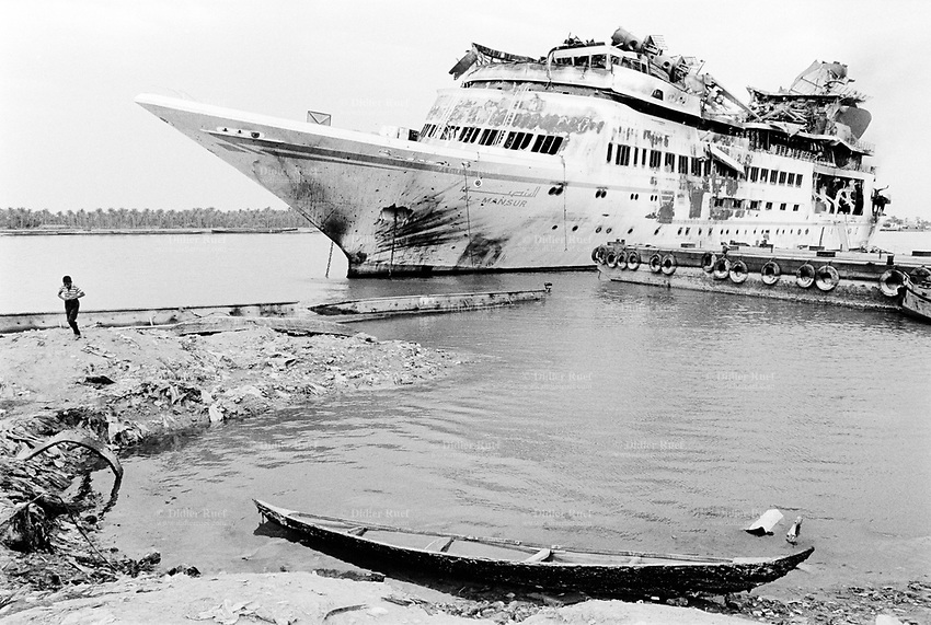 Iraq. Basrah. Shatt Al-Arab river. The Saddam Hussein's yacht was hit by air strikes attacks (missiles) from the coalition forces (american and english army), then later looted and burned by thieves also called Ali-Baba.  © 2003 Didier Ruef