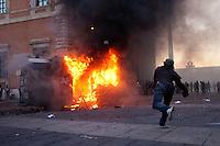 Roma: un manifestante lancia una pietra contro il blindato dei Carabinieri in fiamme dopo un assalto durante il  corteo organizzato dagli indignati. &quot;Occupy Wall Street&quot; &egrave; stata organizzata in 951 citt&agrave; di 82 Paesi per protestare contro la crisi economica mondiale.<br /> <br /> Rome: A demonstrator throws a stone the police van on fire during the demonstration &quot;Occupy Wall Street&quot;