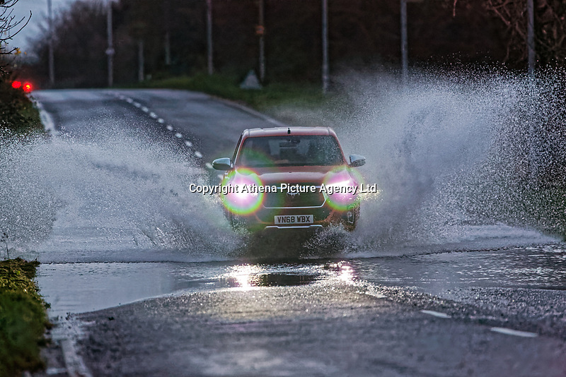 A car travels through a flooded road on the B4283 between Pyle and Port Talbot in south Wales, UK. 07 December 2018