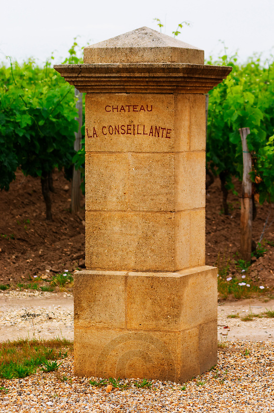 A stone gate post with the inscription Chateau La Conseillante and the vineyard  Pomerol  Bordeaux Gironde Aquitaine France