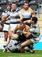 PICTURE BY VAUGHN RIDLEY/SWPIX.COM - Rugby League - Super League - Hull FC v Wigan Warriors - KC Stadium, Hull, England - 22/04/12 - Wigan's Gareth Hock beats the tackle of Hull FC's Sam Moa and Will Sharp to score a try.