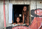 Beatriz dos Santos Rodrigues (left), 18, and her sister Aquida, 9, pose in the widow of their family's floating house, which is tied to a riverbank in Manaus, Brazil. The two girls participate in a Caritas program aimed at preventing sexual abuse and exploitation of children and adolescents. <br /> <br /> Written parental consent obtained.